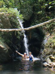 Swimming under Belize waterfall