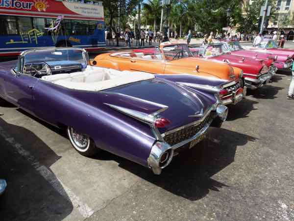 Purple and orange classic cars in downtown Havana